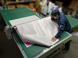 They stick sheets to the boards on a working table like this. When using the UV printer, the printed sheets are stiff and easy to handle.